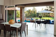 A Luxury Resort-Like Home in Denver I Eurostyle Lovie black resin stacking chairs from Charles Eisen and Associates. Indoor Outdoor Living, Outdoor Decor, Beautiful Dining Rooms, Stacking Chairs, Colorado Homes, Dining Room Lighting, How To Make Light, Beautiful Interiors, Interior Lighting
