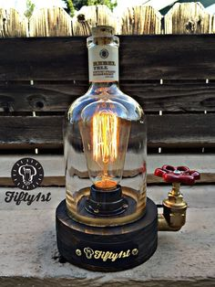 New from Fifty1st is, yep another lamp for your viewing pleasure! Hand crafted reclaimed wood base, brass fittings, water valve switch, vintage cloth cord, reclaimed Rebel Yell whiskey bottle and a whole lot of man sweat! Ever wonder what a creation from Edison would look like if he drank a lot? Well here ya go Lamp Dimensions* Weight: 5lbs Height: 8 inches Width: 4.5 Pipe Fittings: 3/4 brass Valve switch: Brass with red knob Bulb Outlet: 120v/60w max Bulb: Edison style 60 wat