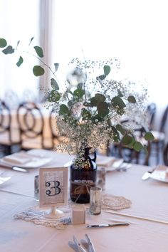 Centerpiece with baby's breath and eucalyptus by Events for You Asheville (in bride's growlers)
