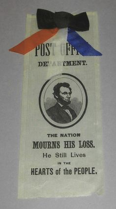 """White silk commemorative ribbon. Black ribbon bow with red, white and blue streamers attached at top edge of ribbon. All text and central image are stamped in black. Text directly below the black bow reads, """"Post Office Department."""" Central image of Lincoln in oval shape. Lincoln with beard in suit in three quarters pose. Text on lower portion of ribbon reads, """"The Nation Mourns His Loss. He Still Lives in the Hearts of the People."""" 7.75"""" x 3.25"""""""