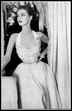 Model Janet Randy in lovely halter necked gown, bodice is appliqued with flowers, by Jo Copeland, Vogue, January 1952