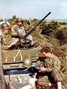 Embarquement sur les navires, début juin 1944 - Operation Overlord . Au premier plan, trois soldats américains dans leur Half-track M3A1 équipé dune mitrailleuse M2 HB Cal.50.