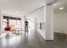 Rotating walls & transforming furniture makes two rooms vanish in this home in Spain.
