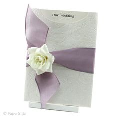 VICTORIAN ROSE  This wedding invitation features an elegant C6 Glamour Pocket in Olivia White Pearl. It is decorated with a beautiful Opaque Lilac 40mm Parasilk ribbon and a plush white velvet rose. The insert is printed on Ice Gold card and simply slides out to reveal your special announcement. The invitation is beautifully presented in a matching Ice Gold invitation box. Price:$7.95 www.facebook.com/...