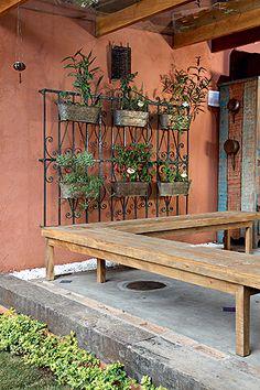 Para receber melhor as visitas, a moradora providenciou o banco de peroba-rosa, que também assume a função de guarda-corpo. Na grade antiga, floreiras de latão acomodam ervas e temperos