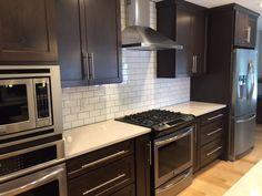 Dark shaker cabinets, white subway tile backsplash, quartz countertop and maple floors. Timeless combo.