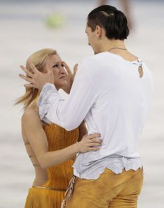 Tatiana Volosozhar and Maxim Trankov of Russia embrace after they competed in the pairs free skate figure skating competition at the Iceberg...