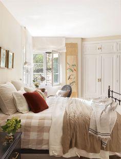 Dormitorio con estructura de cama y mesilla de noche negras, armario, plaids cuadros y escritorio con silla