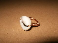 This ring was made with a real brown cowrie sea shell and silver wire. It reminds me of a tropical beach in paradise...very cute for any outfit!  **The cowrie shell has a special place in many cultures. For West Africans it was used as the first money. Native Americans traded African traders us...