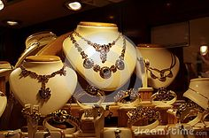 Gold necklaces and bracelets displayed in a jewelry shop window.