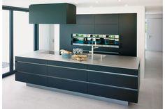 Purismus und klare Linien bestimmen diese Küche mit einer scheinbar schwebenden Insel, schwarzen Glasfronten und einer Arbeitsfläche aus Chromnickelstahl. Brunner Küchen