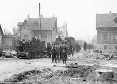 Invasion: British troops advance through the village of Hermanville-sur-Mer, Normandy, June 6, 1944