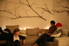 Sticks from the park attached to the wall with red ribbons tied in small bows - A Blog About Love