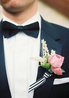 Groom with black bowtie & pink rose & lily of the valley boutonniere w/ stripped ribbon, love.