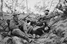 30 Oct 1967, South of Da Nang, South Vietnam --- U.S. 1st Cavalry Infantrymen huddle a group of frightened South Vietnamese children into a ditch to protect them from enemy sniper fire. The battle scene is 10 miles South of Da Nang. --- Image by © Bettmann/CORBIS