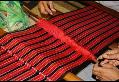 Adjusting the thread on the middle piece of the backstrap loom.