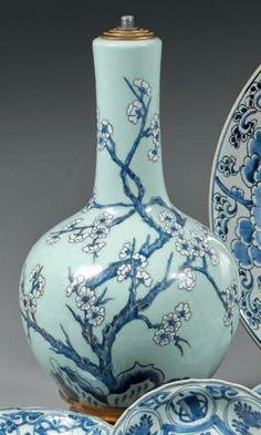 CHINE - XIXe siècle  Vase de forme bouteille en porcelaine émaillée céladon et décorée en bleu sous couverte de branches de pruniers en fl...