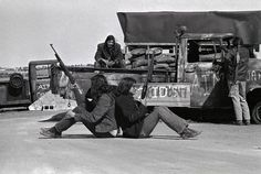 Armed Indians sit back to back supporting one another and keeping eye on all directions as members and supporters of the American Indian Movement (AIM) continue to hold this small village here. These armed militants are at a roadblock leading into Wounded Knee. March 19, 1973.  The occupation and blockade of Wounded Knee began as a demonstration for Lakota rights organized by members of the AIM. Photo credit: Does anyone know who took this image?