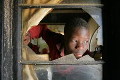 Child headed households   ----   In Zimbabwe, a boy orphaned by AIDS peers out the broken window of his home in Harare, the capital. He lives with his sister and receives assistance from a UNICEF-supported programme that helps child-headed households.   © UNICEF/Giacomo Pirozzi  http://www.unicef.org