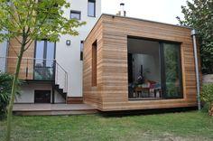 L'extension posée sur la terrasse en ipé, sans lien avec la pelouse, semble flotter au-dessus du jardin.