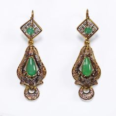 Earrings  Public access description  The colour of the chrysoprases has been enhanced with green material behind the stones in their settings. Made for export to the East with a crescent shape at the bottom of the drop.  Gold, in a variety of treatments, became a dominant element in jewellery from the 1820s. It was used successfully in mesh necklaces and bracelets, gold chain and wire work, also as a foil to gemstones.  The technique of filigree with spirals and granules (cannetille and…