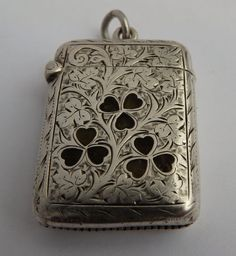 A superb English antique solid sterling silver vesta/match case decorated with beautiful inlaid Irish shamrock agates and with a full set of English silver hallmarks Birmingham 1906. With a sprung hinged lid and further decorated with attractive engraved scroll-work. Complete with its large silver attachment ring.