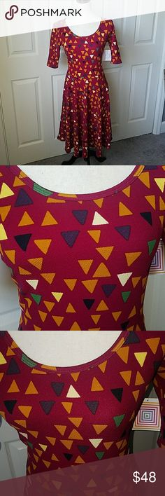 LulaRoe Dress Artsy and beautiful Lularoe Nicole dress. The background is a plum red/ wine color with a fun triangle print that is black, mustard, green, purple and yellow. Never worn,  new with tags.  Size medium. Please refer to attached size chart as Lularoe has special sizing.  ~All sales are FINAL~ Hit that OFFER button now! 😁 LuLaRoe Dresses Midi