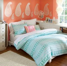 Perfect for a teen or preteen. Love the light peach/coral walls with leaf-like decals and the light teal bed covers with light furniture and medium colored hardwood floor. So much storage and lighting, too!