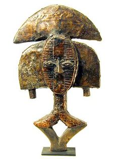 Africa    Bokota reliquary Guardian.  Gabon.  Brass/copper and wood.   These figures were mounted on containers holding relics of important clan ancestors, serving as guardians