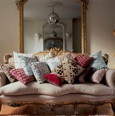Decorative upholstered vintage sofa piled with patterned fabric cushions in a living room with large mirror Exterior Design, Interior And Exterior, Home And Living, Living Room, English Country Style, Vintage Sofa, Lifestyle Store, Interior Photography, Cushion Fabric