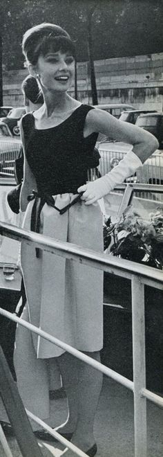 """The actress Audrey Hepburn photographed on the boat """"Bateau Mouche"""" (on Seine) after a press conference for the publicity of her new film """"Paris - When It Sizzles"""". Paris (France), July 16, 1962. Audrey was wearing: Dress: Givenchy (sleeveless, bodice of black satin with a ribbon at the waist in the same tissue and skirt of white silk, of his haute couture collection for the Spring/Summer of 1962)."""