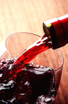 Closeup of red wine pouring in glass - luxury wine accessories at https://www.mimisfifis.com