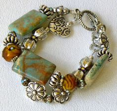 Don't have info on this, but it looks like huge turquoise chunks and beads--lots of matrix there--with tiger's eye beads, and lots and lots of assorted silver beads. Sublime!