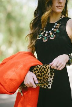 Fashion trends | Chic black dress with statement necklace, orange coat and animal prints clutch