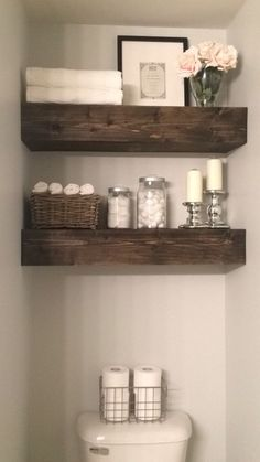 Floating shelves above toilet in bathroom. Much prettier and more useful than the pointless towel bar.