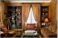 Library with burnt orange walls, black bookcases and a paisley sofa - Tracy Murdock Allied ASID, www.TracyMurdock.com
