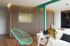 Here, Vázquez poses on a sofa by Avant Haus in the new space. The slatted enclosure houses a bathroom; a one-way mirror lets users see out without forfeiting their privacy.