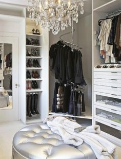 Um yes please!!!! Chic contemporary closet design with crystal chandelier over round tufted silver ottoman ...