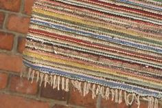 Craft a knotted rag rug using old clothing and rags.