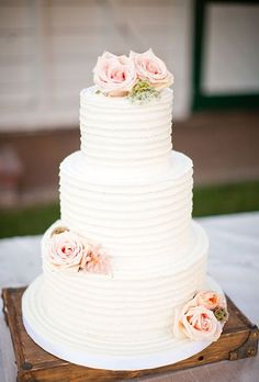 Three-Tiered White Cake with Pink Flowers. A three-tiered white wedding cake decorated with pale pink roses, created by Beverly's Best Bakery.