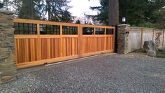 Beautiful, wood slide gate with custom fabricated, wire mesh and digital keypad mounted to the column. Clear cedar infill by Custom Fence and Masonry. #security #gate #driveway #entrance #privacy