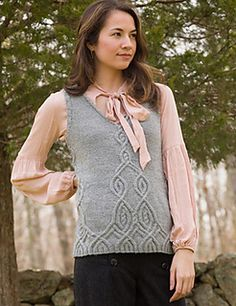 A V-neck vest worked in the round from the bottom up with a diminishing cable motif.