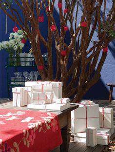 Coberto com uma colcha artesanal, o banco do deque acomoda os presentes. A frondosa jabuticabeira foi escolhida para ser a árvore de Natal. Feitas de redinhas de plástico, as maçãs do amor e as tiras de papel com desejos escritos pelos convidados bastam para compor a decoração dos galhos, que contou com a ajuda das crianças.