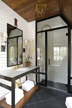 this bathroom has a good,combination of all the materials - white subway tiles, black accent and a wooden ceiling together with brass taps. All the design rules of madaboutthehouse.com in one room