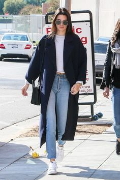 Kendall Jenner wears a cropped sweatshirt, long coat, cropped jeans, Stan Smith sneakers, aviator sunglasses, and a shoulder bag