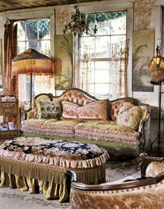 The living room reveals Robin's passion for vintage lamps and pastoral Victorian art. Hand-painted flowers adorn the walls; a carpet remnant tops the fringed ottoman. #countryliving #livingrooms