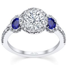 A halo diamond three stone engagement ring is ever more fascinating with sapphire accents as the two side stones in the three stone style.