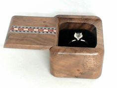 Single Ring Design Walnut Wood with Inlay  This single ring box will hold his or her wedding ring.   Protect and display your ring.  The top is designed so that the lid slides off to revel the rings.  However, each box is crafted so meticulously that the hand-fit dovetail lids remain a visual mystery.  Each lid has a different design, so please contact us for specifics.    Rings not included!  Model #SC8211Heart $30.00  Made in the USA