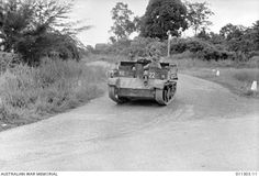 An Australian Army Bren Gun carrier moving up along a rural road for first contact with Japanese forces.