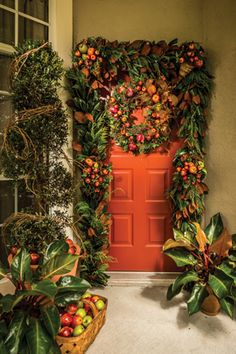 """FALL HARVEST Garland and matching wreath with faux fruit """"horns of plenty."""" Rojo Congo philodendrons, a potted Eugenia topiary wrapped with grapevine, and a basketful of faux apples complete the ornamentation."""